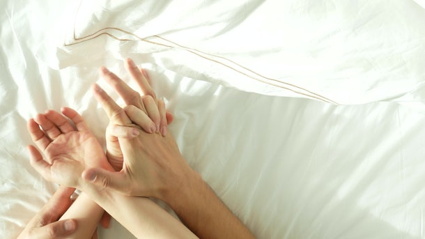 Hands of couple making love. Man and woman having sex. top view