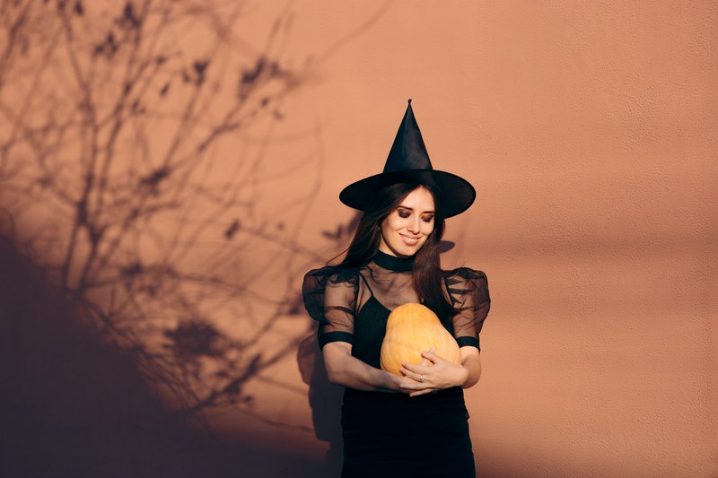 Halloween Woman in Witch Costume Holding Pumpkin. Party host organizing autumn holiday celebration in October