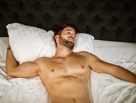 Young handsome Caucasian with sexy muscle body shirtless laying on the white bed showing off his great body