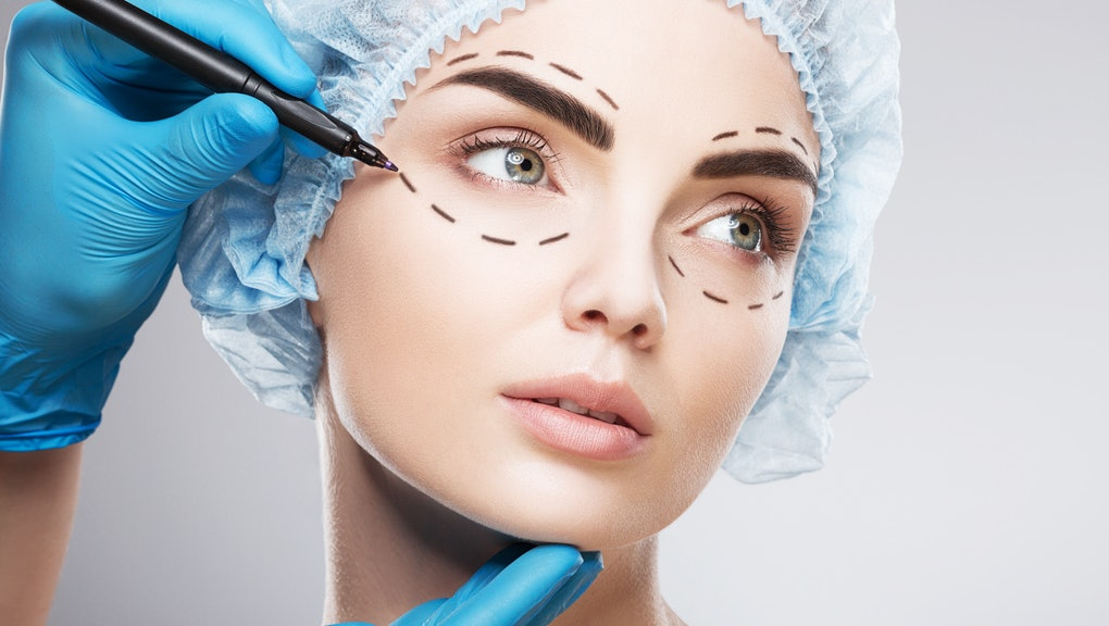 Amazing girl wearing blue medical hat at studio background and looking right, perforation lines on face, close up, plastic surgery concept, doctor's hand in glove making marks on patient's face.