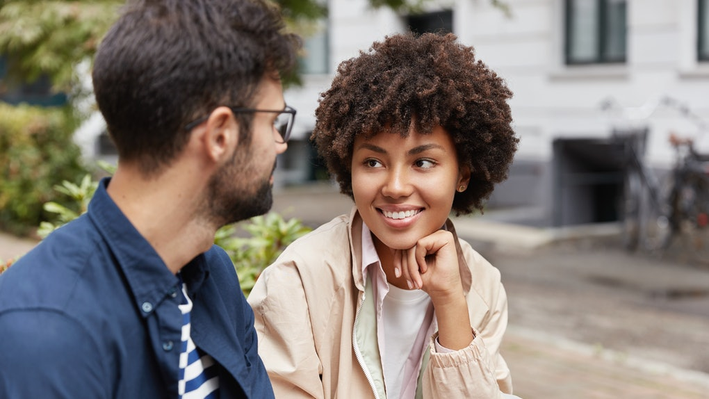 Photo of mixed race tourist enjoy lively communication, discuss traditions of their countries, eat fastfood on street, being in good mood. Beautiful Afro American girl talks with handsome guy outdoor