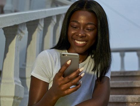 Nice black woman looking her smartphone
