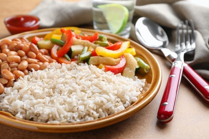 Plate of brown rice with beans and vegetables on table. Going vegan means you need to make sure you get enough nutrients.
