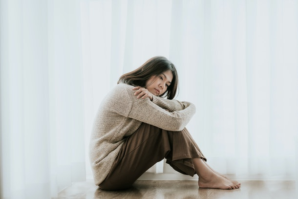 Sad Asian woman with depression sitting alone on the floor. major depressive disorder