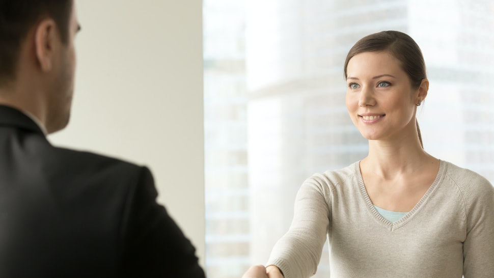 Attractive millennial woman handshaking with man in business suit. Confident young businesswoman welcoming business partner before negotiation at company office. Female job applicant first impression