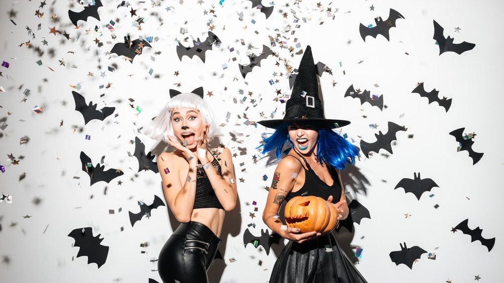 Two women dressed up for Halloween — one as a cat and one as a witch — smile as confetti falls around them.