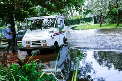 A postal worker returns to their truck parked on a flooded street a few miles from the downtown Miam...