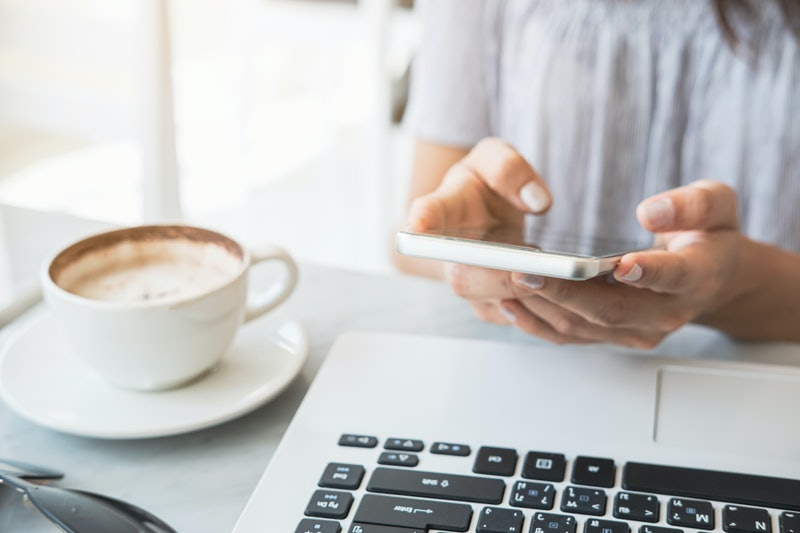 Young woman using smart phone and laptop with cup of coffee in cafe