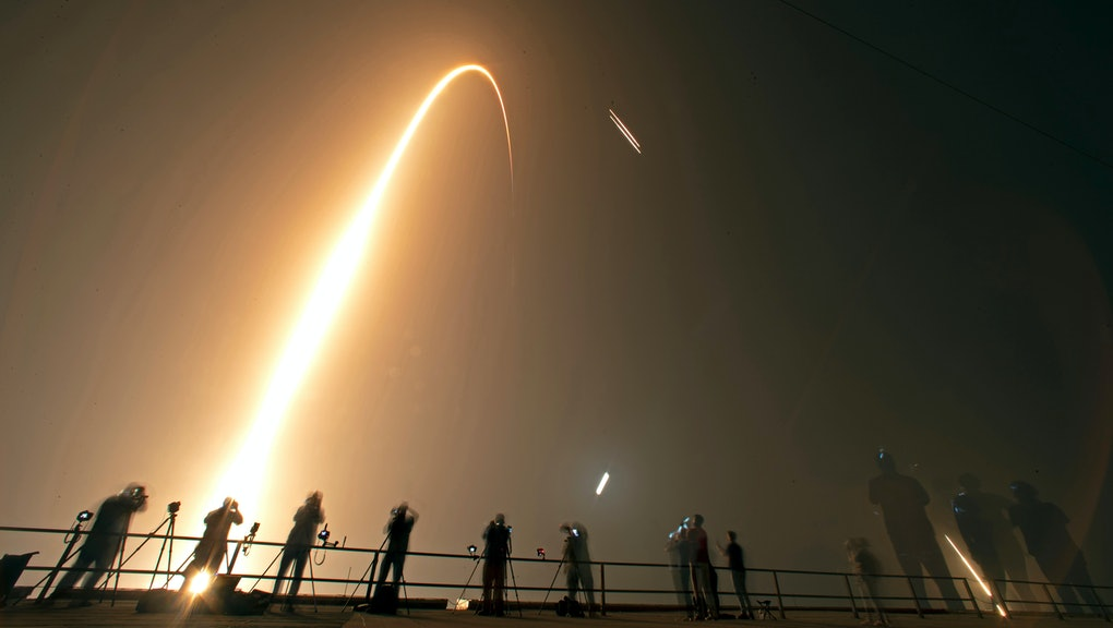 Photographers on the roof of the Vehicle Assembly building capture the launch and rocket boosters landing of a SpaceX Falcon heavy rocket at the Kennedy Space Center in Cape Canaveral, Fla., . The Falcon rocket has a payload military and scientific research satellites