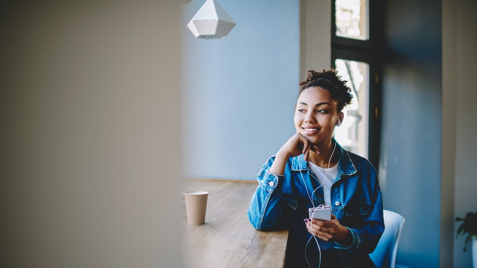 Positive female teenager looking away and dreaming about big love while listening romantic music song via electronic earphones, happy woman holding cellular gadget and enjoying time in coffee shop