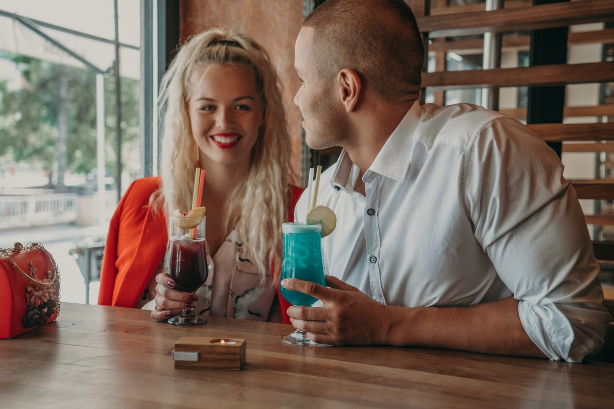 Young african man and blonde american woman drink cocktail, happy couple in bar drink cocktail and have fun