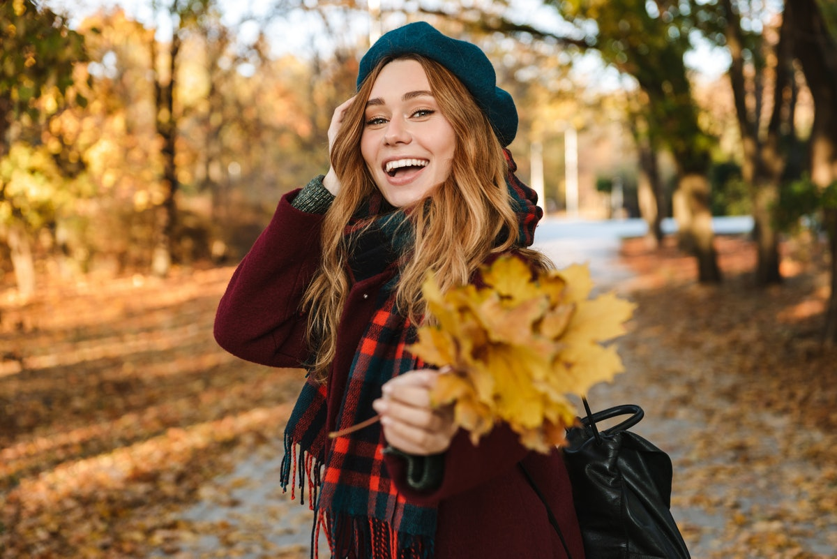 Cheerful young girl with long brown hair wearing autumn coat, walking at the park