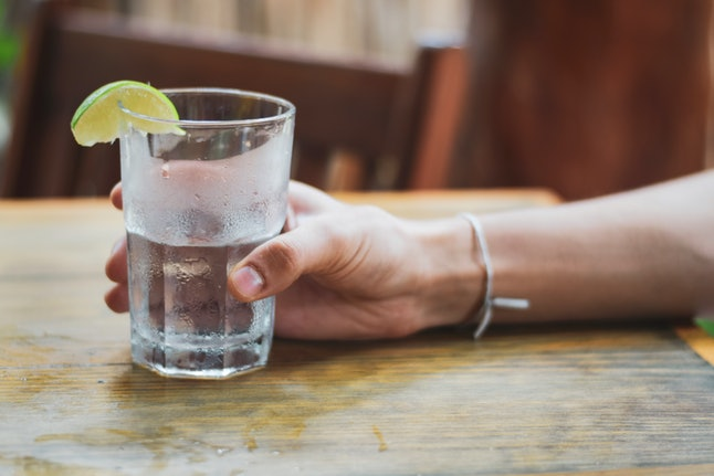 Male hand holding water glass with condensation with lime wedge outside.