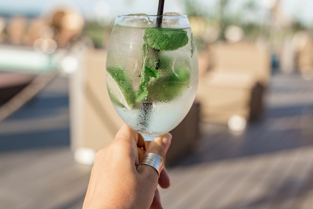 Transparent cocktail with bubbles and lime in the hand of young woman.