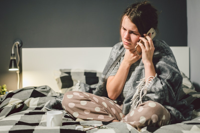 respiratory diseases and home remedies. young woman sick with cold sitting bedroom on bed holding throat sadness emotion. Sore throat man takes pills. Call phone, ask for help doctor. Call ambulance.
