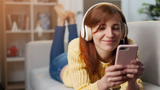 Cheerful young woman in headphones listening to music with his smartphone. Girl in headphones is listening to music and smiling while lying on couch at home.