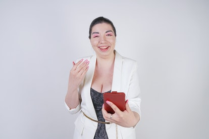 charming mix race plus size woman in a white business jacket standing with smart phone in hand on wh...