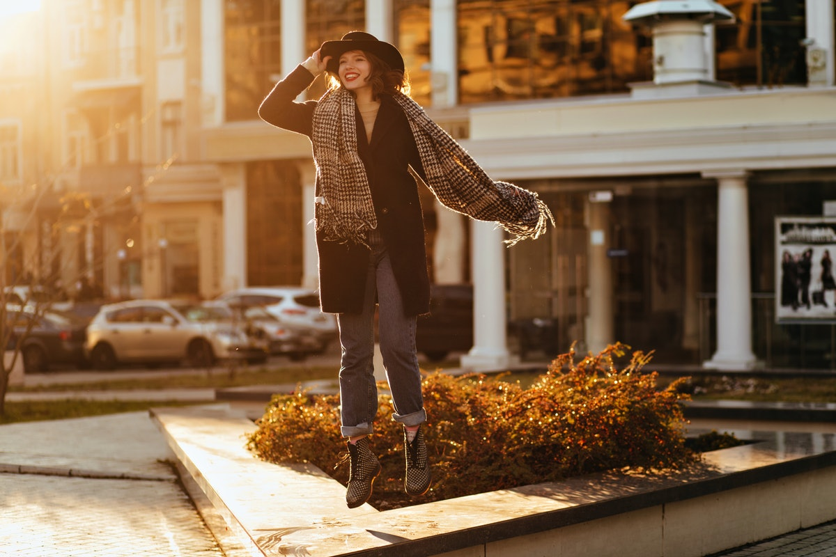 Enthusiastic girl in black coat and hat expressing happiness. Outdoor portrait of beautiful lady wea...