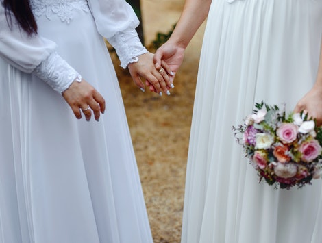 Same sex gay couple having their wedding, wearing dresses.