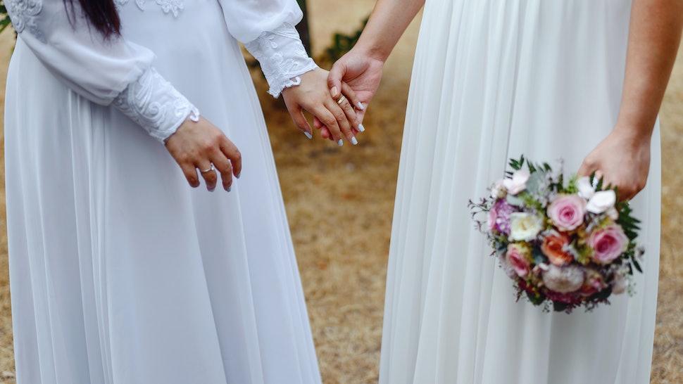 Same sex gay couple having their wedding, wearing dresses.