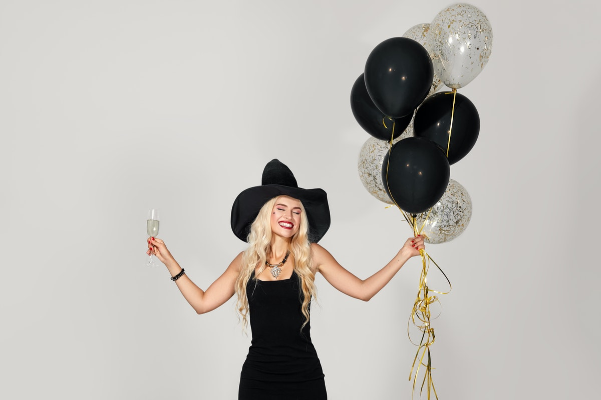 A blonde woman is dressed in a black dress and black witch's hat, which is a perfect last-minute Halloween costume.