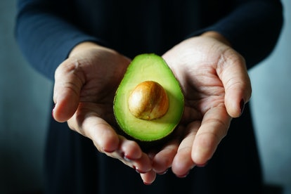 Fresh cut avocado in hands of woman in black dress with blurred dark grey background. Being vegan isn't something to apolozie for