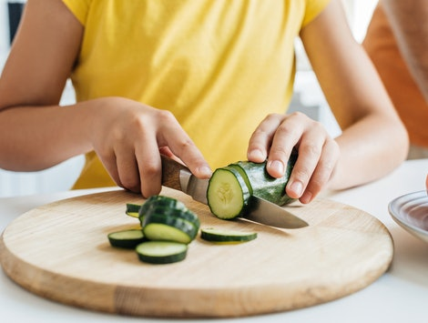 cropped shot of girl cutting cucumber with knife