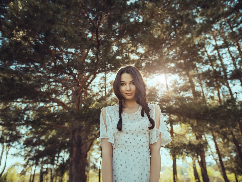 Free happy woman in forest enjoying nature. Natural beauty girl outdoor in freedom enjoyment concept. Mixed race Caucasian Asian girl posing on travel vacation holidays in dress.
