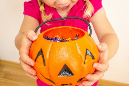 A little girl holds a pumpkin with candy in her hands and stretches it to get even more candies for ...