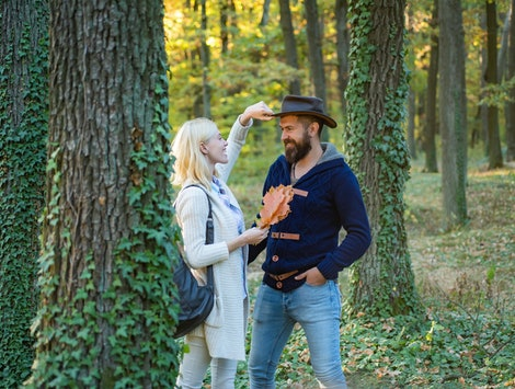 Young couple with autumnal mood. Passion dating and love. Autumn and leaf fall Dreams. Portrait of beautiful woman and man walking outdoors
