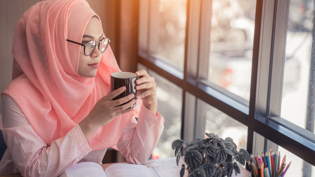 Arab women in hijab holding and drinking coffee cup sitting in the coffee shop