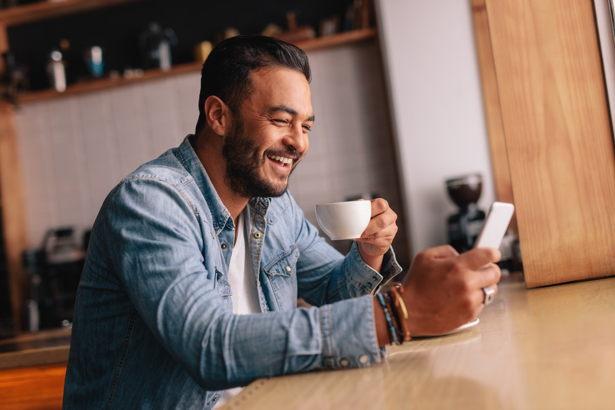 Smiling young caucasian man sitting at cafe using mobile phone and having coffee. Handsome male with cup of coffee and reading text message on his smart phone.