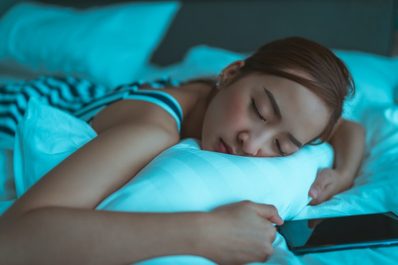 Close up portrait of a woman tired and sleeping in an hotel bed with a mobile phone