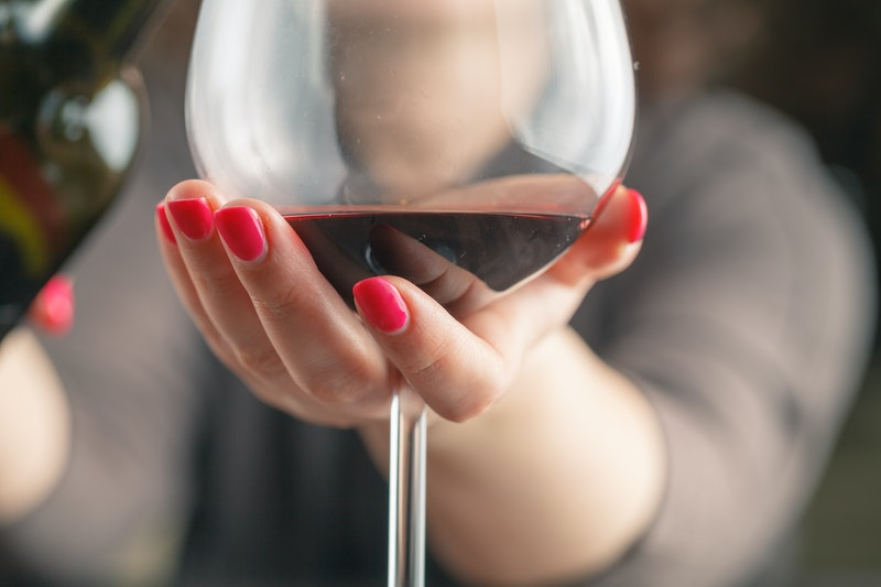 waitress pouring red wine in a glass