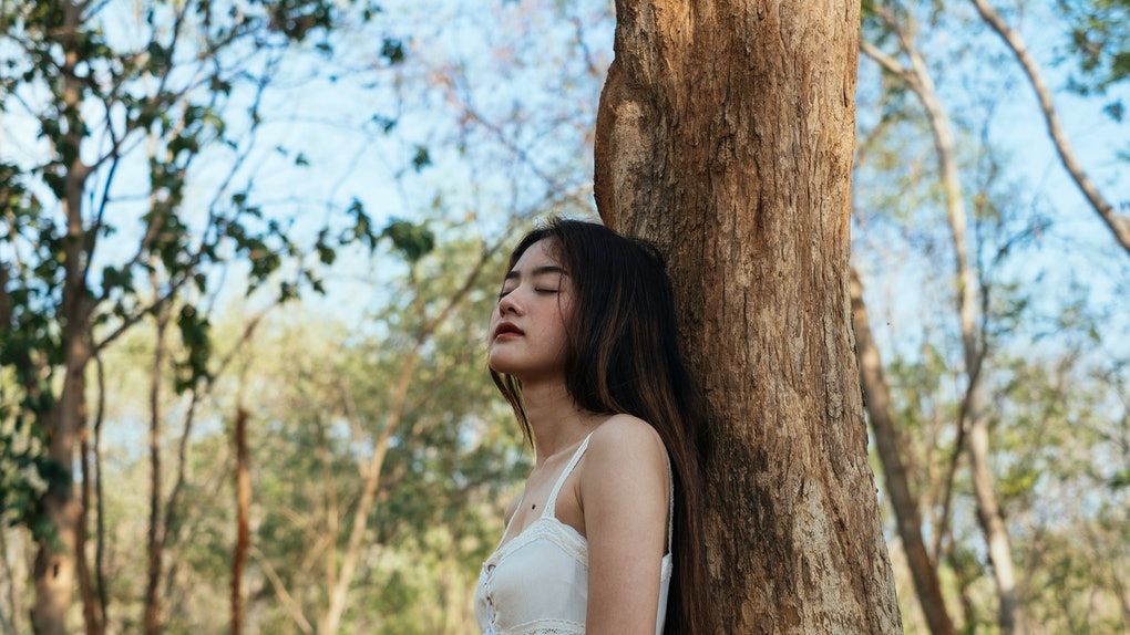 Girl closing her eyes leaning against a tree under shadow.