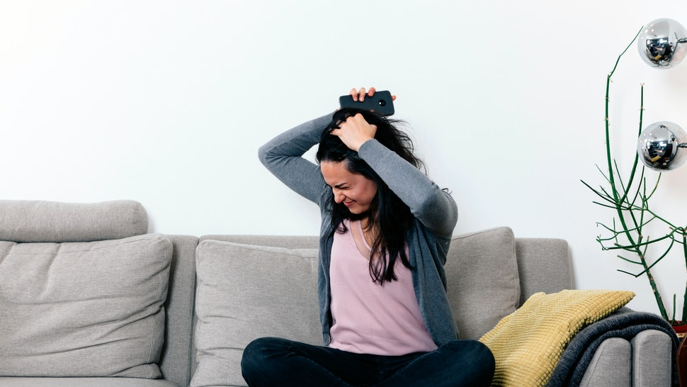woman on a couch with angry and desperate face, holding a mobile phone and teraing her hair