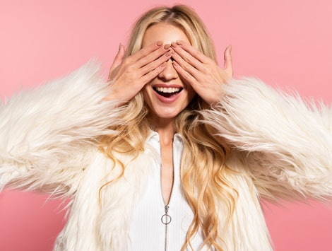 happy beautiful blonde woman in white faux fur jacket with hands on eyes isolated on pink