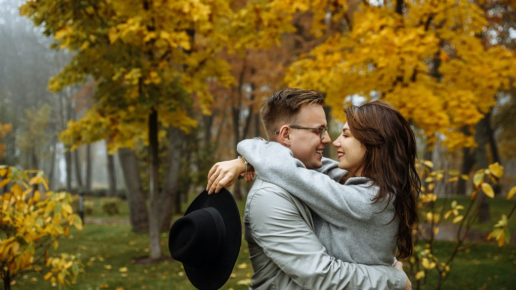 Loving couple in stylish casual wear hugs in the park in the autumn season. Autumn. Golden autumn. Golden leaves.