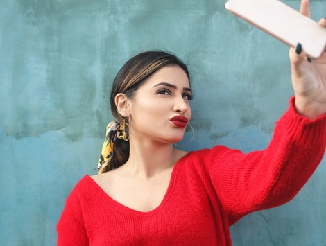 Girl taking a selfie with her smart phone. Instagram is removing filters associated with plastic surgery.