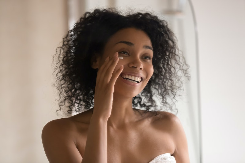 Smiling african American young woman wrapped in towel after shower look in mirror apply under eye anti-aging cream, happy biracial female perform morning skincare beauty procedures at home