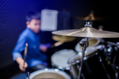 Selective focus to cymbals of drum set with blurry kid learning and play drum set with teacher in music room. The concept of musical instrument.