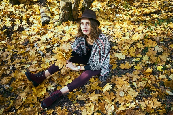 A brunette woman in maroon boots and leggings sits in a pile of yellow leaves in the fall.