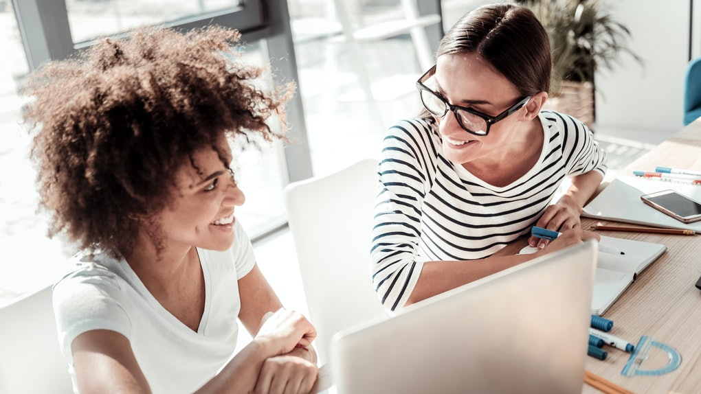 Pleasant partnership. Joyful nice pleasant women looking at each other and smiling while sitting in front of the laptop