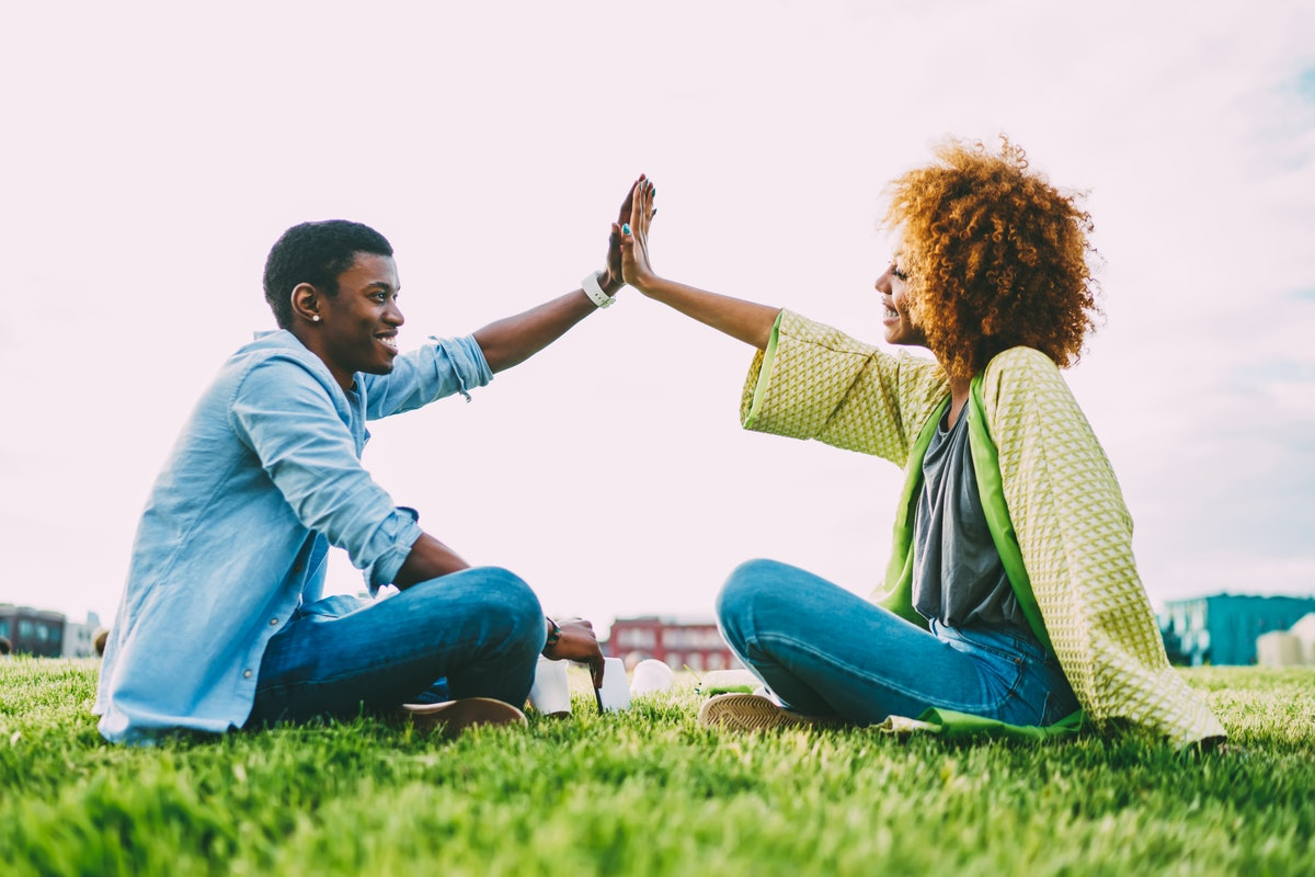 Happy african american friends raising hands up giving high five sitting on green grass lawn on sunny day, trendy dressed dark skinned hipsters celebrating success during meeting outdoors in city park