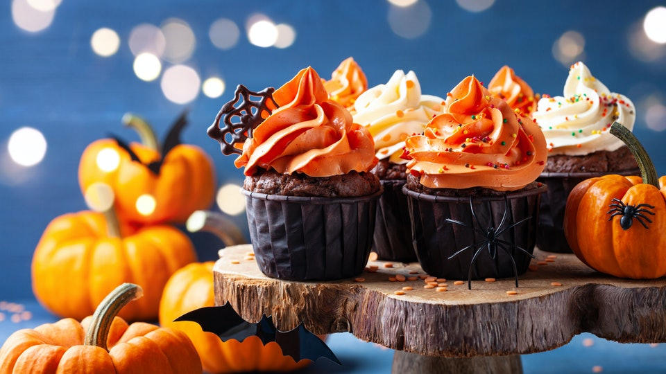 Halloween cupcakes and pumpkins on dark blue background. Sweets for holiday party.
