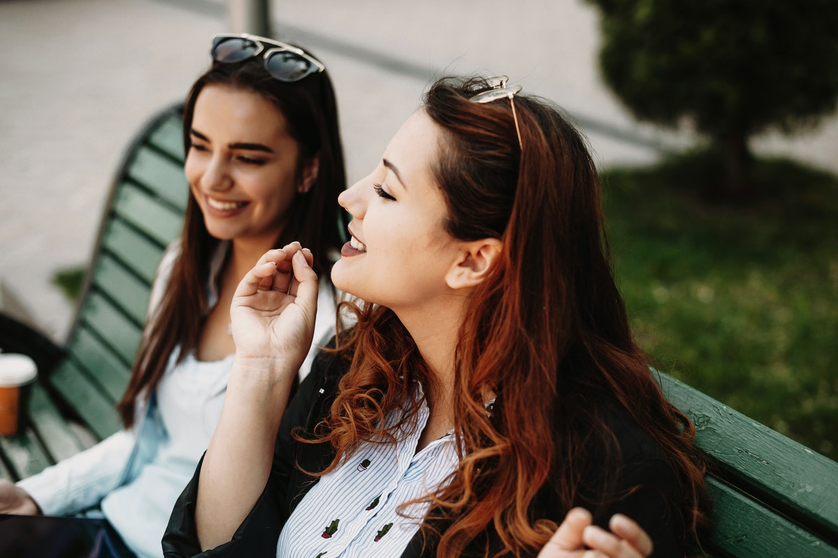 Close up portrait of a amazing plus size woman with red hair storytelling something captivant to her girlfriend while sitting on a bench.