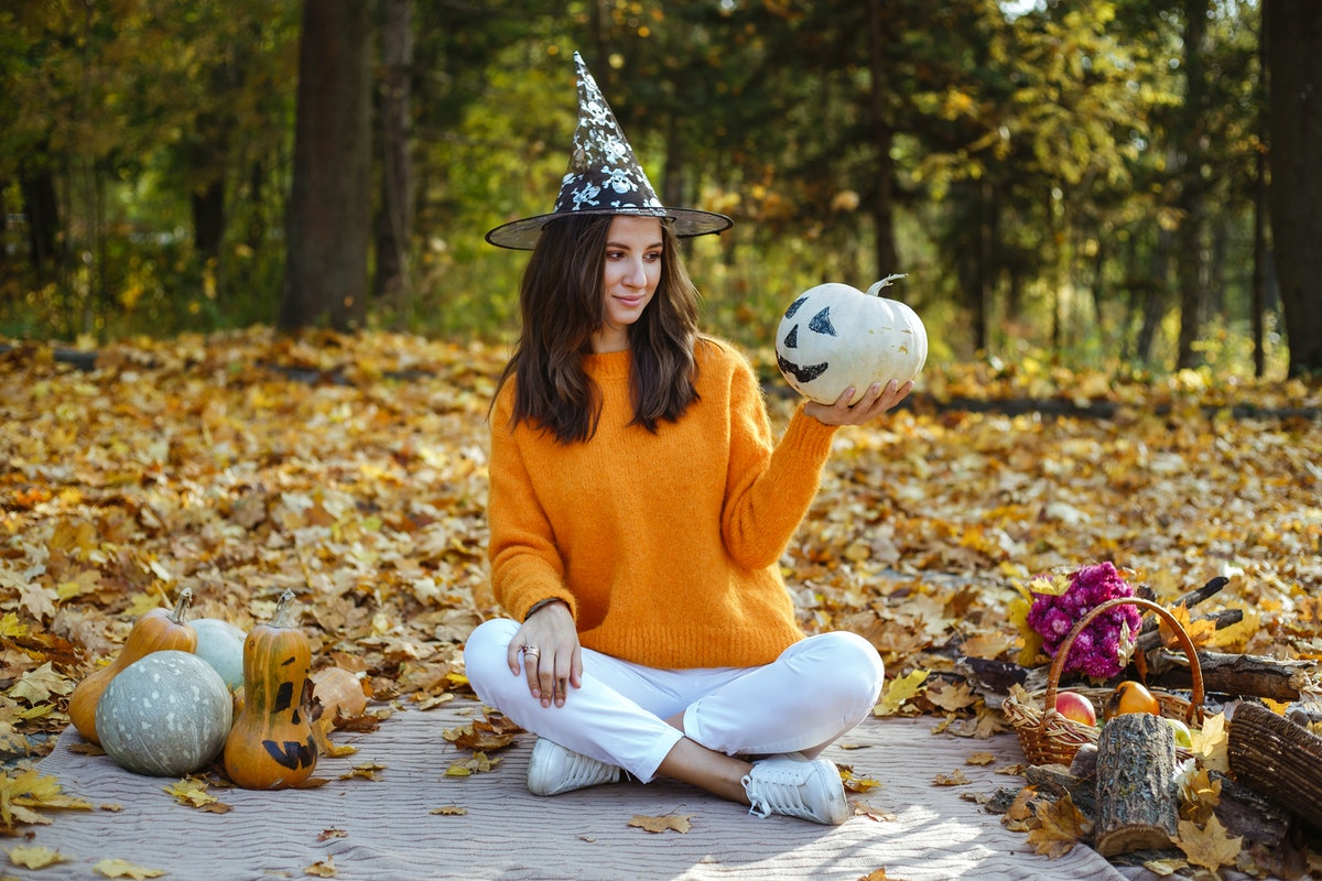 A girl sits outside on Halloween in white jeans, an orange sweater, and a witch hat and holds a pumpkin.