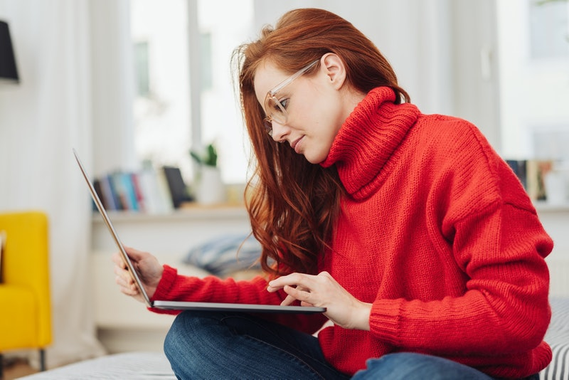 Young woman in a bright red winter sweater sitting working on a laptop on a bed at home in a close up cropped profile view