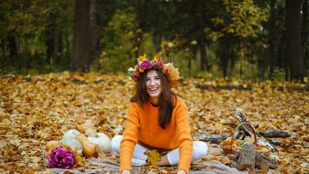 Happy girl throws yellow leaves up, autumn season.