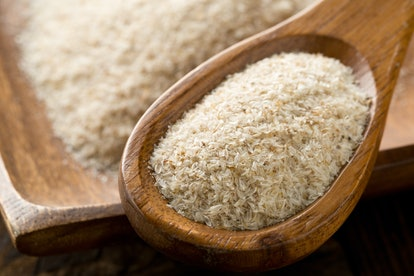 Heap of psyllium husk in wooden spoon and bowl on table. Psyllium husk is a natural remedy for constipation